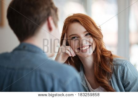 Young cheerful female student listening her boyfriend in cafe
