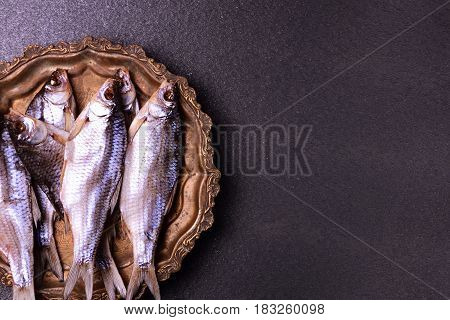 Dried in salt fish ram on scales on a copper tray empty space on the right