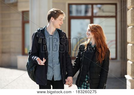 Smiling students holding hands each other and talking in the street