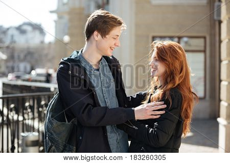 Cheerful couple of young cute students hugging in the street