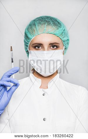 Concentrated female doctor or scientist in white medical gown, blue gloves, green cap and mask holds a syringe in hand on white background. She is ready to give an injection