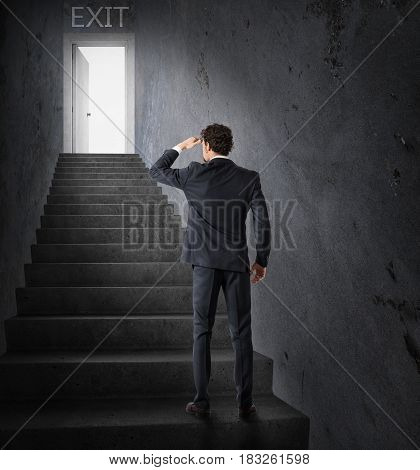 Businessman looks at the exit at the end of the stairs. Exit from business stress and financial crisis