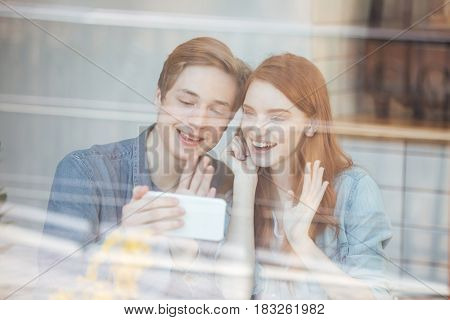Portrait of funny couple sitting by the table in cafe behind the glass and making selfie on smartphone