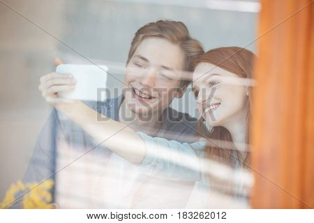 Portrait of students sitting in cafe behind the glass and making selfie on smartphone