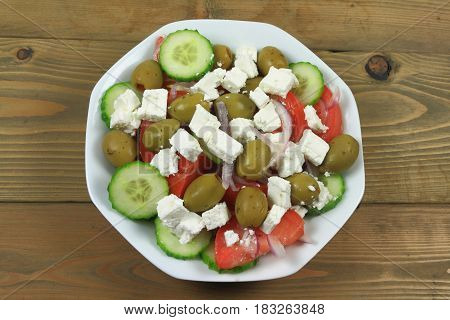 Greek salad from fresh organic vegetables: chopped red onion tomatoes cut on wedges sliced seedless cucumber; and stuffed green colossal olives cubes goat Feta Cheese in white dish on wooden table