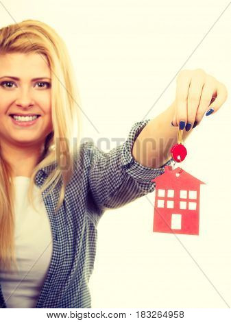 Ownership and property concept. Happy woman holding red paper house and keys moving to new home.