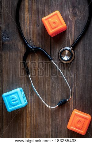 Pediatrician workplace with stethoscope and toys on wooden table background top view