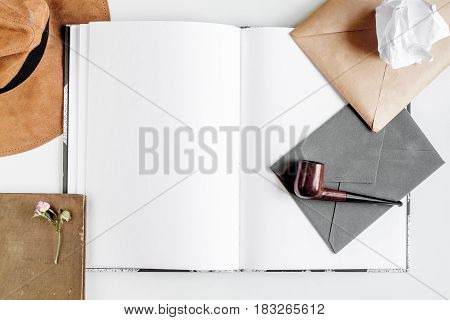 Writer workplace with tools, copybook, pipe and envelope on white table background top view mock up