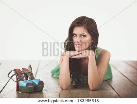 Beautiful young woman in dress lying on the floor.