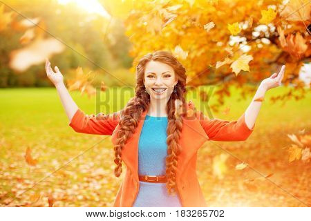 Autumn woman on background fall landscape leaves of trees. Girl Model on autumn season. Fashion people.