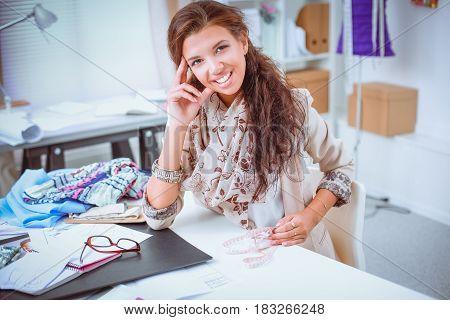 Smiling female fashion designer sitting at office desk .