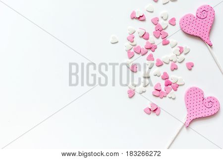 Closeup of a heartshaped lollipop with candy and chewing marmelade on white table background top view mockup