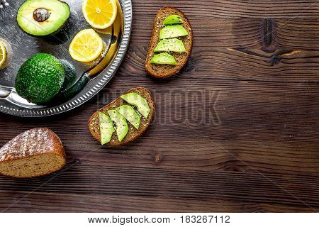 Ingredients for cooking sandwiches with fresh avocado on wooden kitchen table background top view mockup