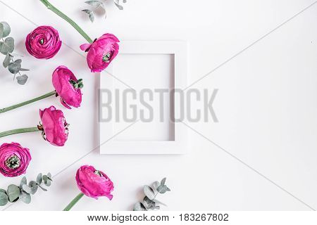 Modern spring design with bright pink flowers and frame on white desk background top view moke up