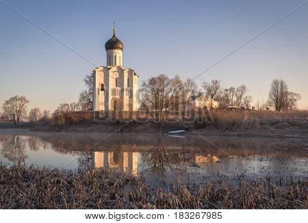 Ancient White Church On The Shore Of The Lake In The Frosty Dawn