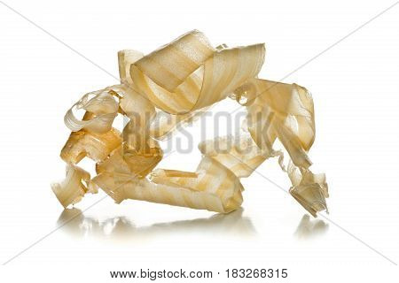 Light brown wood shavings from carpenter's hand planer or chisel work on wooden boards on white background with selective focus