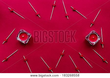 scarlet collection with candles on red colored desk background top view space for text