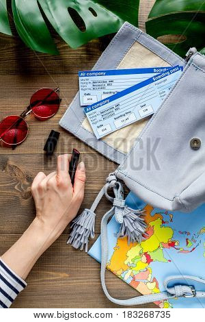 tourist stuff with worldwide map and flight tickets on wooden table background top view
