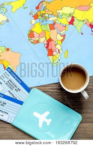 journey planning with tourist outfit and flight tickets, map and passport on wooden table background top view