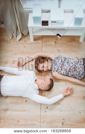 Happy young couple lying together on the floor.