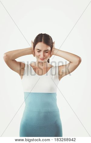 Portrait of a stressed woman standing isolated on a white background.
