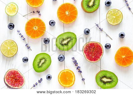 Citrus fruit pattern with orange, lime kiwi, fig, lavender and blueberry on white wooden desk background top view