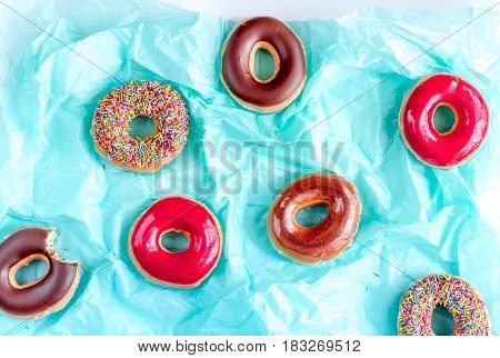 strawberry and chocolate donuts with topping on blue paper background top view pattern