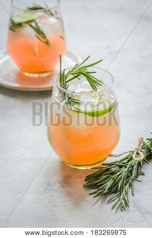 sliced lime, rosemary and natural juice in glass on stone kitchen table background