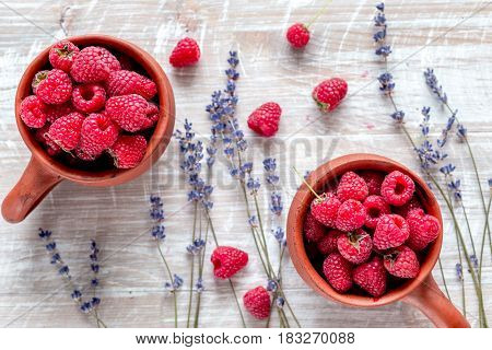 raspberry in pottery cup and vase with lavender on light wooden table background top view