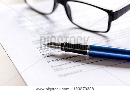 office desk with signing contract, glasses and feather pen for business