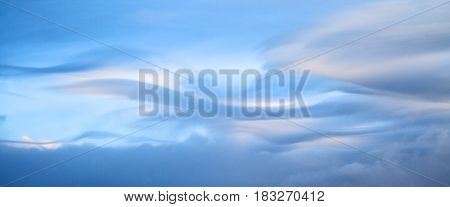 Beautiful wavy clouds in the morning light background in soft colors