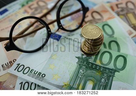 Selective focus on stacked of Euro coins with Euro banknotes and glasses as finance concept.
