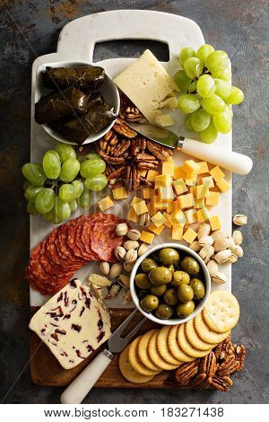 Cheese and snacks platter with fruit and nuts overhead shot