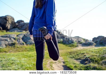 Young Fitness Woman Stretching her Legs on the Rocky Trail in Sun Rays. Female Runner Doing Stretches Outdoor. Healthy Lifestyle Concept.