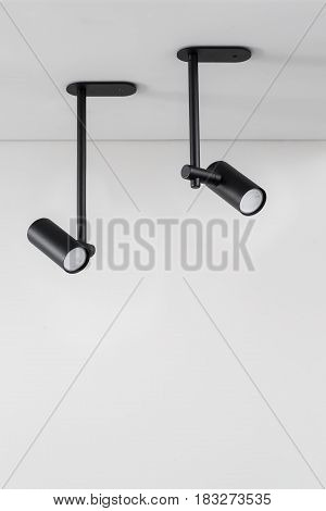 Two black lamps are hanging on the ceiling on the gray wall background. Closeup photo. Indoors. Horizontal.