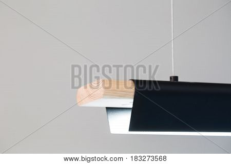 Glowing light wooden lamp with a bended black metal part is hanging on the rope on the gray background. Closeup photo. Horizontal.
