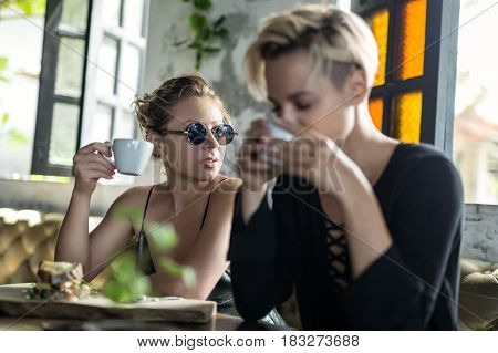 Attractive girls are relaxing in the cafe. They are drinking from white cups. On the table there is a wooden board with a sandwich. One girl wears sunglasses. Sunlight shines on them. Closeup.