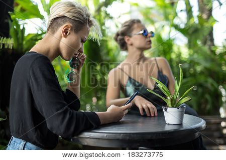 Delightful girls by the round table in the cafe with many green plants. One girl in sunglasses looks to the side, other holds sunglasses and a cellphone. Daylight shines on them. Closeup. Horizontal.