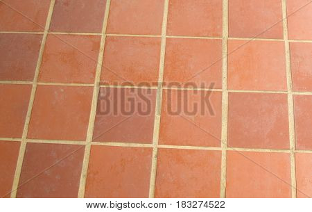 Square floor tiles in a variety of ochre shades.