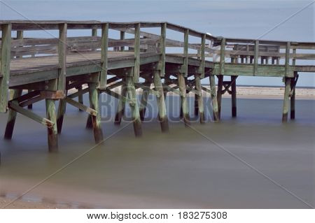 A wooden dock on the beach leading out into the bay