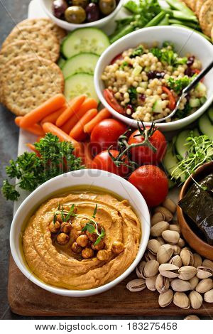 Hummus and fresh vegetables snack platter with grain salad and crackers
