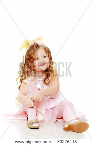 Beautiful, chubby little girl with long, blond, curly hair.Dressed in a pink dress and a bow in her hair.Girl sitting on floor and wearing new shoes.Isolated on white background.