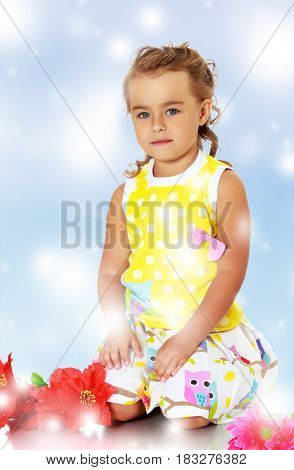 Beautiful little girl in a yellow summer dress kneeling on the floor. Beside her lay a red artificial flowers.Blue Christmas festive background with white snowflakes.
