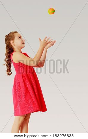Cute little girl in a bright orange dress, throws a little ball.On a gray background.