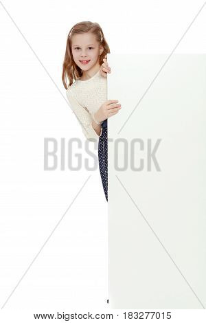 Cute little Caucasian girl hiding behind a large banner.Isolated on white background.
