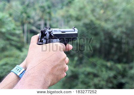 gun in man hand over blurry background