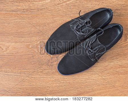 Black mens shoes on a wooden floor. The view from the top.