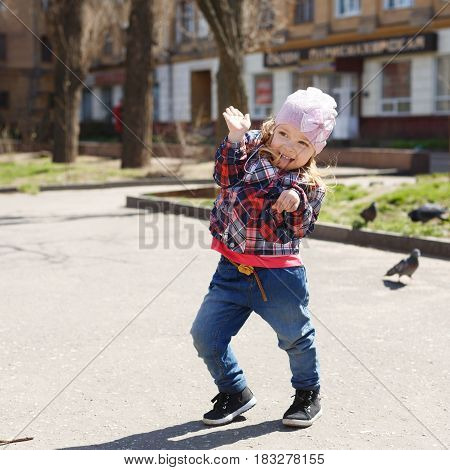 Little girl walks in the park. She is posing and fooling around. Spring mood. Outdoors.
