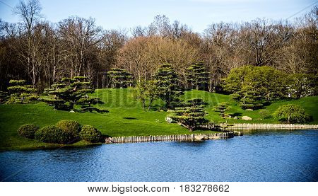 Blue lake with green relaxing landscape, threes and blue sky.