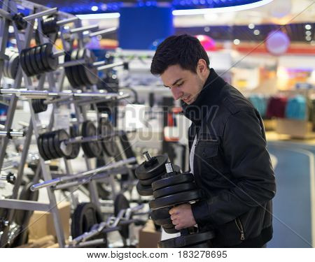 portrait of young male customer choosing dumbbells at supermarket store